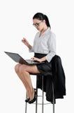 Geschäftsfrau, die auf einem Stuhl sitzt und einen Laptop betrachtet weiß Lizenzfreie Stockbilder