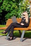 Geschäftsfrau, die auf einer Bank sitzt Lizenzfreie Stockfotos
