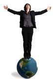Geschäftsfrau, die auf einer Erdekugel steht Stockfotografie