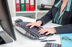 Geschäftsfrau, die auf einer Tastatur schreibt Lizenzfreies Stockbild