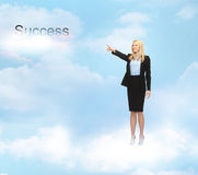 Geschäftsfrau, die auf Erfolgswort im Himmel zeigt Lizenzfreies Stockfoto