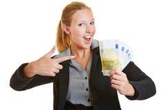 Geschäftsfrau, die auf Eurogeld zeigt Lizenzfreies Stockfoto