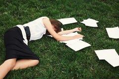 Geschäftsfrau, die auf Gras liegt Stockbilder