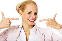 Geschäftsfrau, die auf ihr glückliches Lächeln zeigt Lizenzfreie Stockbilder