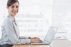 Geschäftsfrau, die auf ihrem Laptop am Schreibtisch schreibt und an der Kamera lächelt Lizenzfreie Stockfotografie
