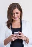 Geschäftsfrau, die auf ihrem Mobiltelefon schaut stockfoto
