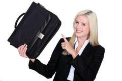 Geschäftsfrau, die auf ihren Aktenkoffer zeigt Lizenzfreies Stockbild