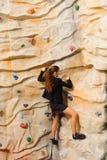 Geschäftsfrau, die auf künstlicher Klippe klettert Stockbild