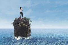 Geschäftsfrau, die auf Korallenriff in Meer steht Stockfotografie
