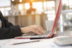 Geschäftsfrau, die auf Laptop-Computer an Bürocafé, nahes u schreibt Stockfotografie