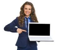Geschäftsfrau, die auf Laptopleeren bildschirm zeigt Stockbild