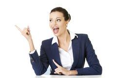 Geschäftsfrau, die auf leeren Exemplarplatz zeigt Lizenzfreie Stockfotografie