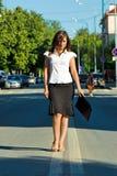 Geschäftsfrau, die auf Mitte der Autostraße geht Stockfotografie