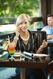 Geschäftsfrau, die auf Mobile im Kaffee spricht Lizenzfreie Stockbilder
