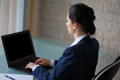 Geschäftsfrau, die auf Seitenansicht des Laptops schreibt Stockfoto
