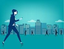Geschäftsfrau, die auf Stadt unter Verwendung eines intelligenten Telefons geht Lizenzfreie Stockfotografie