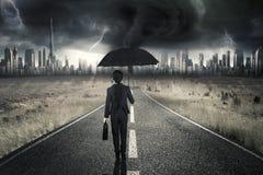 Geschäftsfrau, die auf Straße mit Gewitter geht Stockfotografie