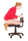 Geschäftsfrau, die auf Stuhl spielt Stockbild