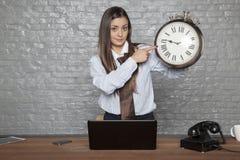 Geschäftsfrau, die auf Uhr, Anzeige für Nachzügler zeigt stockfoto