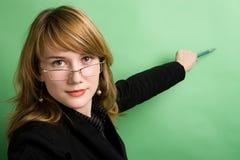 Geschäftsfrau, die auf Wand zeigt Lizenzfreie Stockfotos