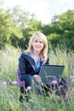 Geschäftsfrau, die auf Wiese mit Laptop sitzt stockbilder