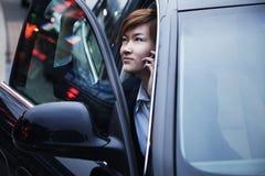 Geschäftsfrau, die Auto während am Telefon herausnimmt Stockbild