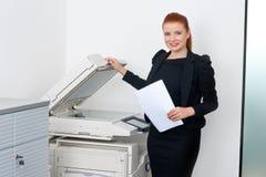Geschäftsfrau, die an Bürodrucker arbeitet Stockfotos
