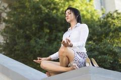Geschäftsfrau, die barfuß meditiert Stockfoto