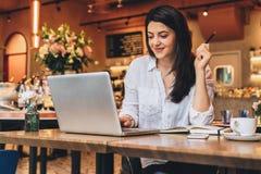 Geschäftsfrau, die bei Tisch im Café, schauend auf dem Schirm des Computers sitzt und lächeln Telearbeit Online-Marketing, Bildun Lizenzfreie Stockfotografie