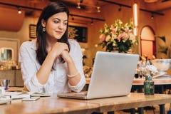 Geschäftsfrau, die bei Tisch im Café, schauend auf dem Schirm des Computers sitzt und lächeln Telearbeit Online-Marketing, Bildun Stockbilder