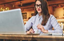 Geschäftsfrau, die bei Tisch im Café vor Laptop, trinkender Kaffee sitzt Mädchen, das, online lernend blogging ist und überprüfen Stockbild