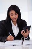 Geschäftsfrau, die Berechnungen tut Stockfotografie