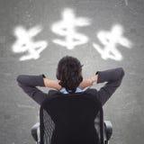 Geschäftsfrau, die bewölkte Dollarsymbole betrachtet Lizenzfreie Stockfotografie
