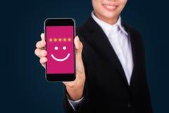 Geschäftsfrau, die Bewertung mit glücklicher Ikone, Kunde satisfacti gibt stockfotografie