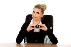 Geschäftsfrau, die Billardkugel acht durch einen Schreibtisch hält Stockbild