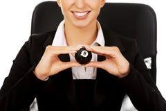 Geschäftsfrau, die Billardkugel acht durch einen Schreibtisch hält Stockbilder