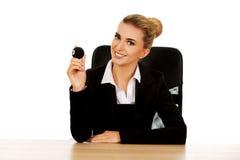 Geschäftsfrau, die Billardkugel acht durch einen Schreibtisch hält Lizenzfreie Stockfotografie