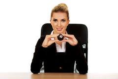 Geschäftsfrau, die Billardkugel acht durch einen Schreibtisch hält Stockfotos