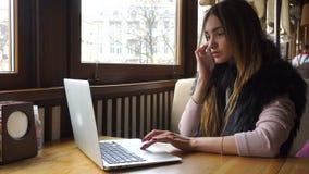 Geschäftsfrau, die am Computer arbeitet und am Telefon spricht stock footage
