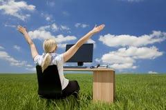 Geschäftsfrau, die Computer auf einem grünen Gebiet verwendet Lizenzfreie Stockbilder