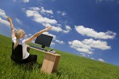 Geschäftsfrau, die Computer auf einem grünen Gebiet verwendet Stockfotografie
