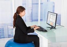 Geschäftsfrau, die Computer beim Sitzen auf Eignungsball verwendet Stockfotos