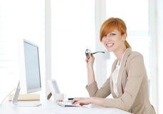 Geschäftsfrau, die am Computer sitzt Lizenzfreie Stockbilder