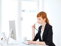 Geschäftsfrau, die am Computer sitzt Stockfotos
