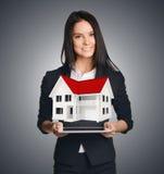Geschäftsfrau, die das Haus symbolisiert Verkauf von zeigt Stockfoto