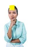 Geschäftsfrau, die das signe auf ihrer Stirn betrachtet Stockfotos