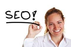 Geschäftsfrau, die das Wort SEO schreibt Stockbild