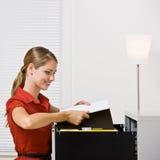 Geschäftsfrau, die Datei in Dateikabinett einsetzt Stockbild