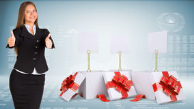 Geschäftsfrau, die Daumen-oben zeigt Öffnen Sie Geschenkkästen Stockfotografie