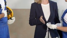 Geschäftsfrau, die dem Erbauerteam für die Arbeit ein Geld steht an der Baustelle gibt stock video footage